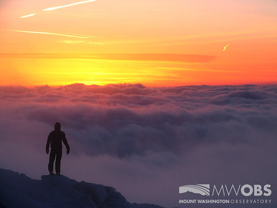 A Mount Washington Observatory weather observer stands on a rock outcropping to view the undercast and the setting sun.