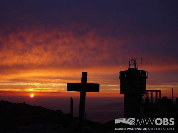 Silhouettes of the Mount Washington summit sign and Mount Washington Observatory weather tower as the sun sets during a summer day.