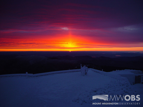 A sun pillar as the sun rises over the Sherman Adams Observation Deck.