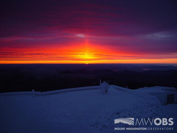 A sun pillar as the sun rises over the Sherman Adams Observation Deck.