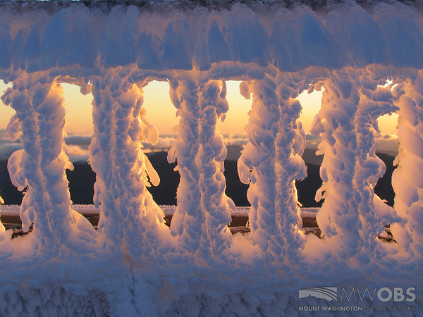Sunrise light on rime covered deck railing.
