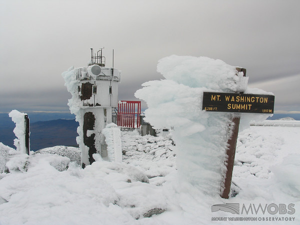 Long feathers of rime on the Mount Washington Summit sign with the Observation tower in the background.